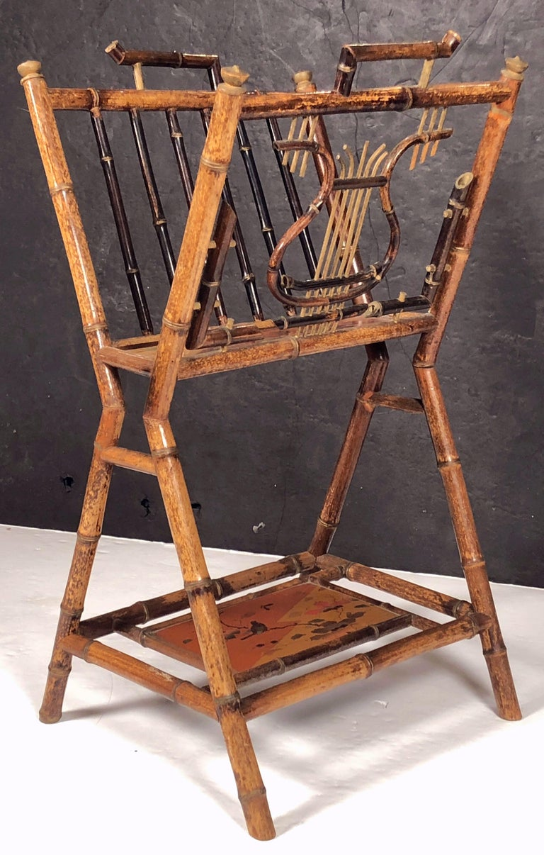 A fine English bamboo Canterbury music stand or magazine rack featuring a bamboo stand with a lyre design in bamboo, with lacquered chinoisierie panel under-tier and stretcher base, and decorative caps.