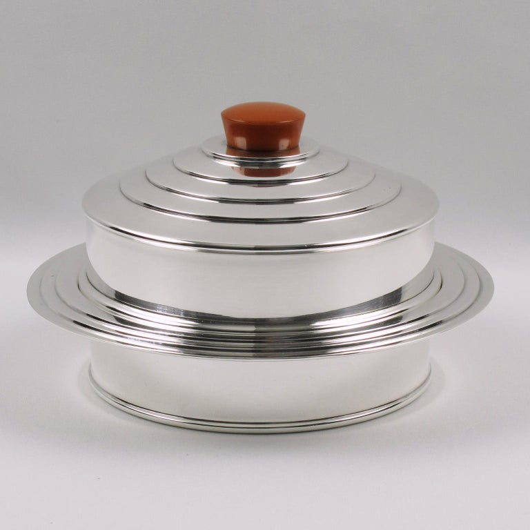 Lovely English Art Deco decorative box by Barker Brothers, Birmingham. Round shape with embellished tiered stepped border on base and same embellishment on cover. Lid topped with large orange Bakelite finial. Marked underside: EPNS, Made in England