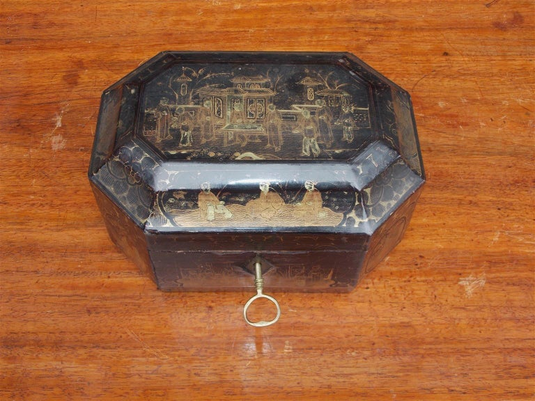 English octagonal hinged black lacquered tea caddy with gilt stenciled figural pagoda, decorative foliage motif, original hand chased lidded interior pewter container with bone knob, and exterior locking key. Early 19th century.