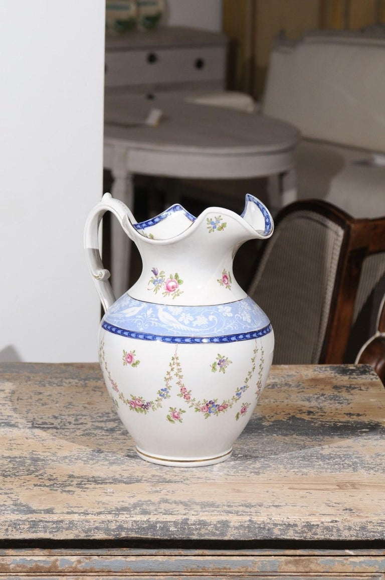 An English Booth's silicon China cameo pattern pitcher from the early 20th century, with pink roses and blue and white pheasants. Born in England during the early years of the 20th century, this exquisite pitcher features a lovely decor made of