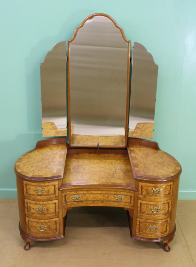 A charming burr walnut kidney shaped dressing table in the Queen Anne style. Well made in solid walnut with attractive burr walnut veneers. The triple mirrors are adjustable and in excellent order. The table is of kidney form and has an arrangement