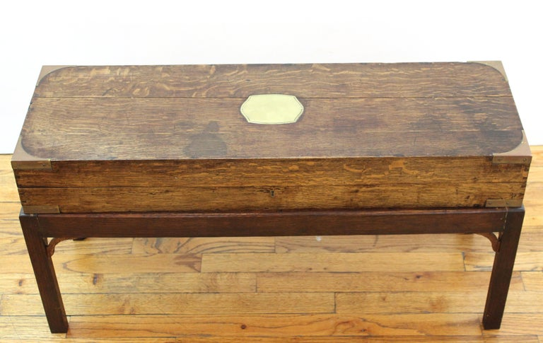 English campaign chest style storage box with brass inlay top, placed on pedestal legs, used as diminutive coffee table or cocktail table. Use and wear to the green felted interior.
