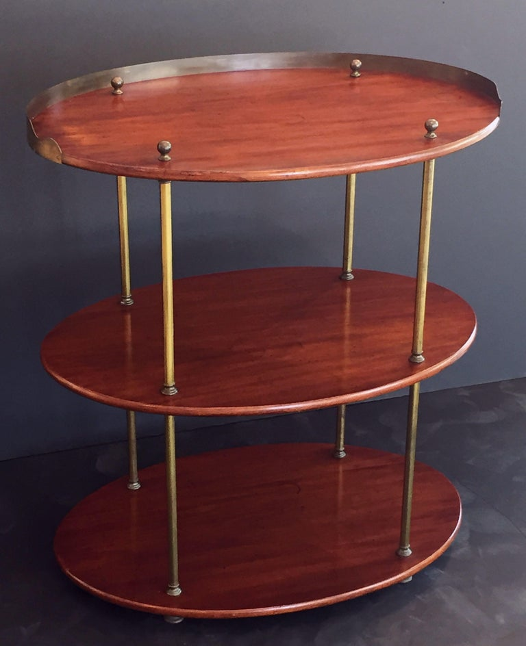 A Fine English Campaign ware or ship captain's table or three-tiered tray table of mahogany and brass, featuring an oval top with a brass gallery, over a middle and bottom tier, mounted by four stylish brass column posts, with round finial tops and