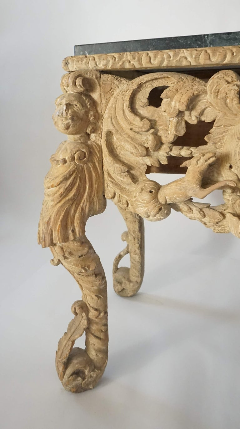 English Charles II Carolean Restoration period console or side table in original lime wash finish on elaborately carved base supported by carved putto and acanthus terms joined on sides by winged putto heads in acanthus aprons; the front with deep