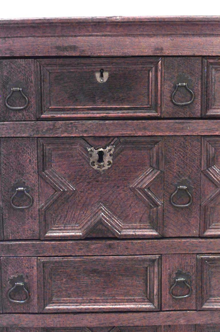 English Charles II style oak chest of drawers with four geometric fronted drawers above an apron on bracket feet.