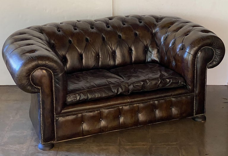 A fine, comfortable English Chesterfield sofa in vintage brown or tobacco leather featuring button-tufted back and arms, two soft leather fitted seat cushions, and beaded-nail trim design, resting on turned feet with casters.  The Chesterfield