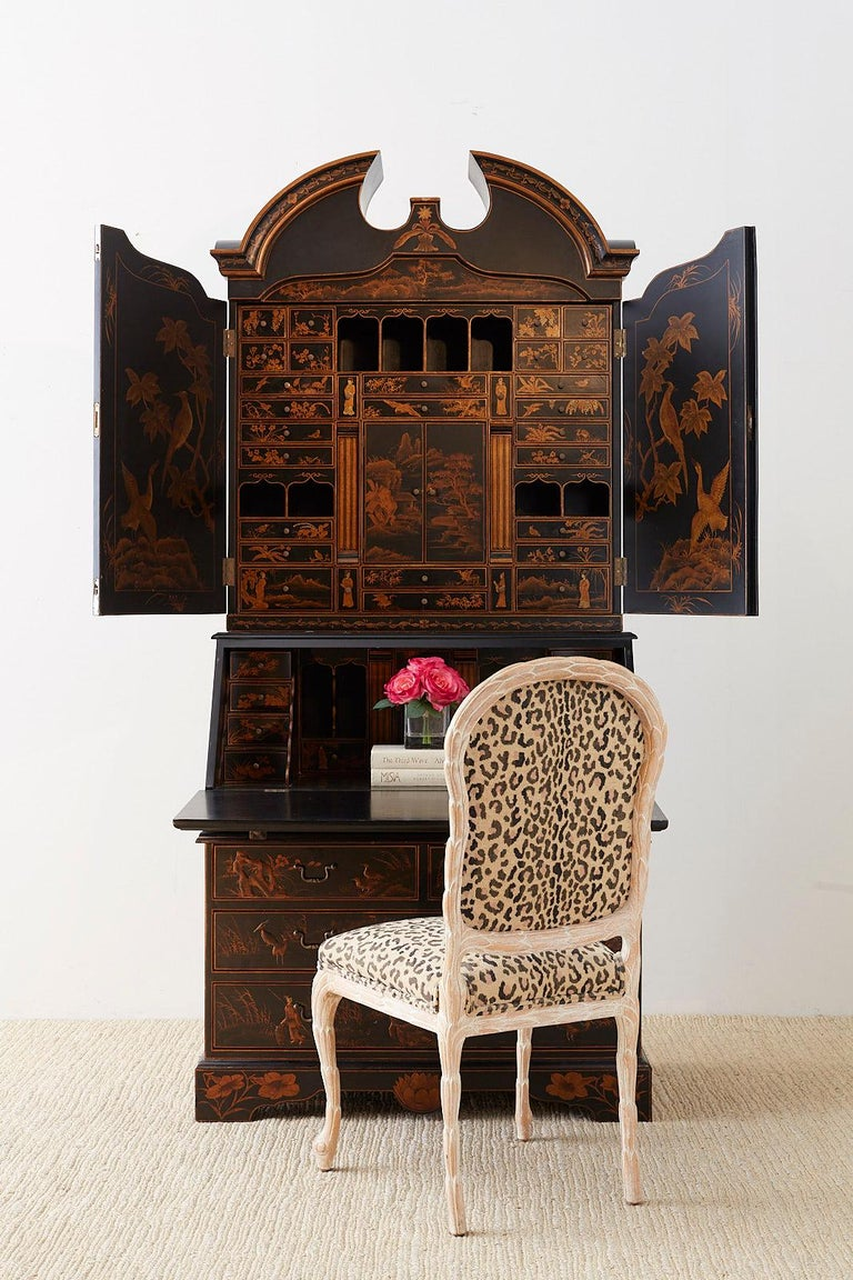 Grand English Georgian style lacquered secretaire featuring a parcel gilt decoration in the chinoiserie taste. The top of the case has a broken pediment over two decorated doors. The fitted interior has multiple felt lined storage drawers, pigeon