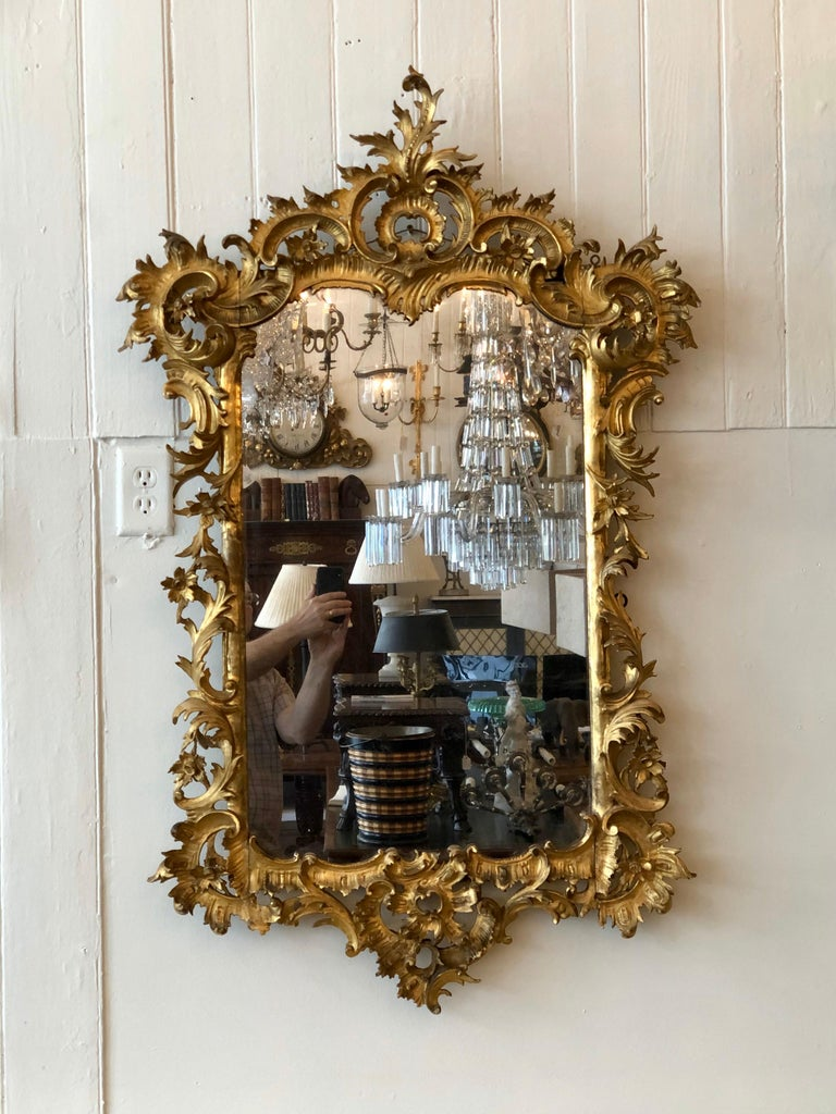 English Chippendale Rococo mirror with carved wood gilded frame. The gilded wood frame is of the finest carving with an acanthus leaf cartouche and cabochonon, intertwined with 'C' scrolls, and acanthus leaf framing the looking glass.