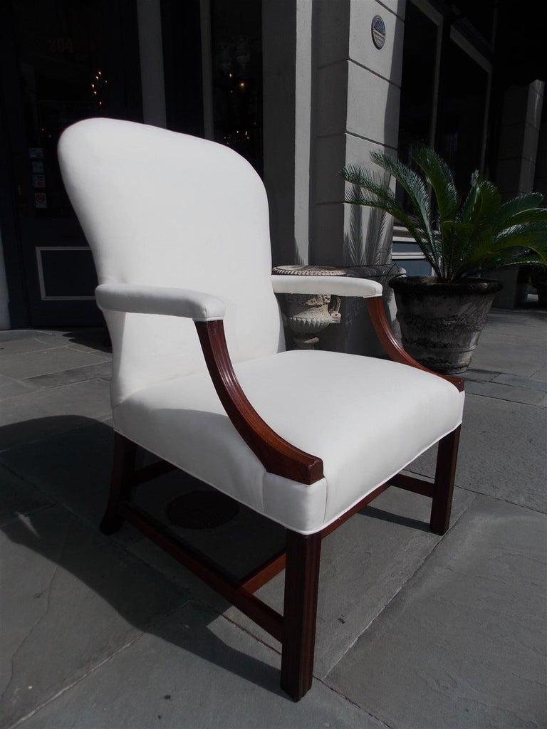English Chippendale mahogany spoon back library chair with flanking scrolled fluted arms and resting on fluted squared legs, splayed rear legs with the original connecting stretchers. Chair is upholstered in white muslin with horse hair and cotton