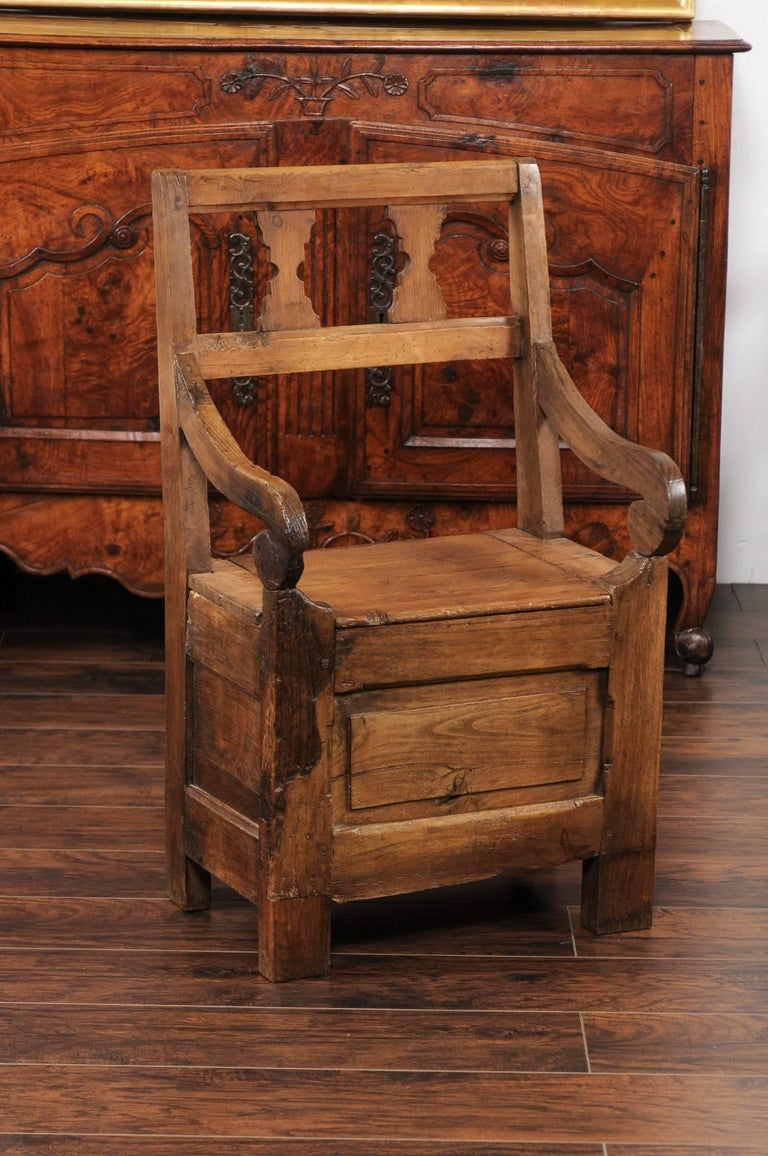 An English country pine chair from the early 19th century, with pierced back, scrolled arms and lift-top seat. This rustic country armchair features a simple pierced back, adorned with hourglass-shaped motifs. Two elegant scrolled arms connect the