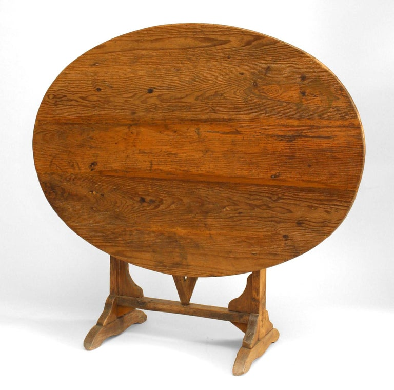 English country style (19th century) oval pine tilt-top end table with trestle base.