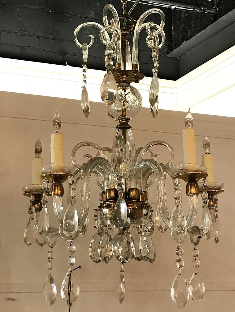 Lovely English brass, blown glass, and crystal chandelier. The crown with blown glass loops with suspended almond-shaped prisms atop a shaped stem surmounted with scrolled arms having cut crystal bobeche decorated with bead and pear-shaped prisms.