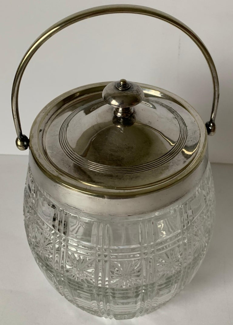 English cut glass and silver plate biscuit barrel. Clear cut glass. Silver plate lid and handle. No makers mark or signature.