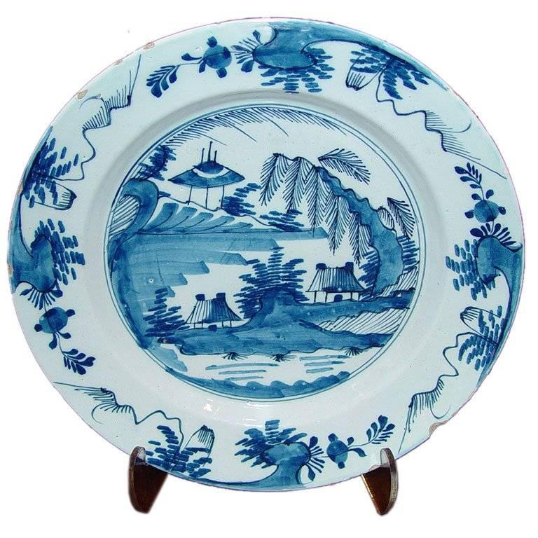 Good quality 18th C English blue and white Delft charger depicting cottages on a river.