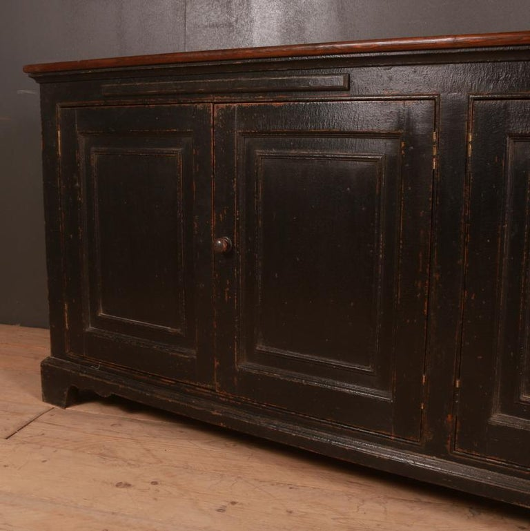 19th century English 4 door dresser base with 2 slides, 1840.   Dimensions: 86.5 inches (220 cms) wide 17 inches (43 cms) deep 35 inches (89 cms) high.
