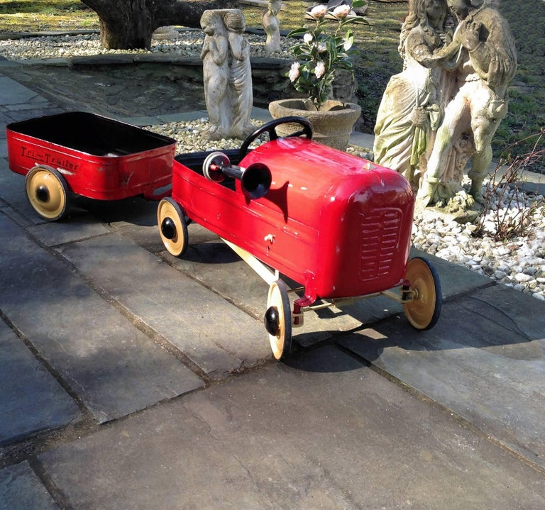 This is a wonderful opportunity to acquire British made 1950s pedal car and matching trailer. Professionally restored to enhance the patina and show off its Classic colors and contours. Embellished with a vintage air horn. The pedal car and trailer