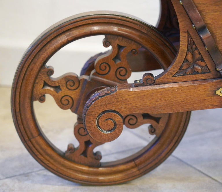 This early 20th century English Edwardian carved mahogany wheel barrow was used for the transport and display of books in a library setting. It is artfully crafted with brass-clad wheel and decorative brass hardware, carvings and turned axel. It