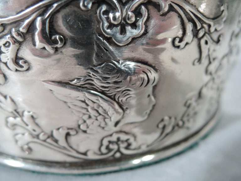 Edwardian sterling silver wine bottle coaster. Made by William Comyns in London in 1903. Straight sides and molded rims. Encircled with floral garland inset with winged cherub heads. Stained-wood well has central silver frame with engraved armorial.