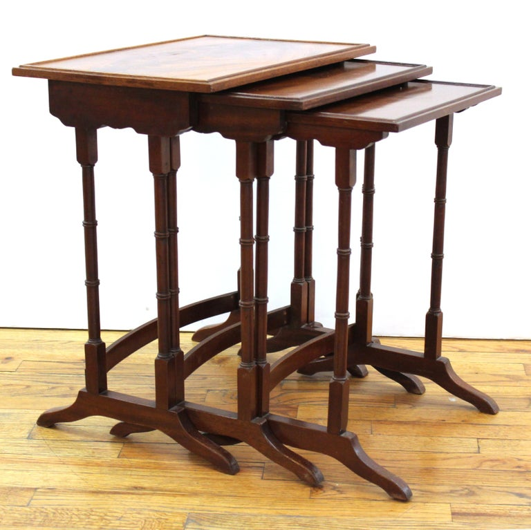 English Edwardian set of three nesting tables with curved cross stretchers.