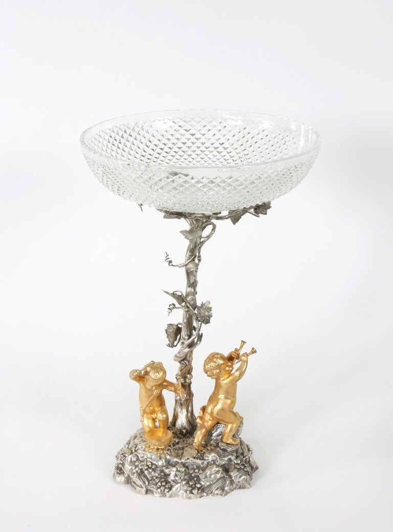 English Elkington silver plated / cut crystal tableware centerpiece with two standing putti playing instruments at the foot of an ivy wrapped tree. The piece is in great antique condition . maker's mark undersigned . The piece stand about 16