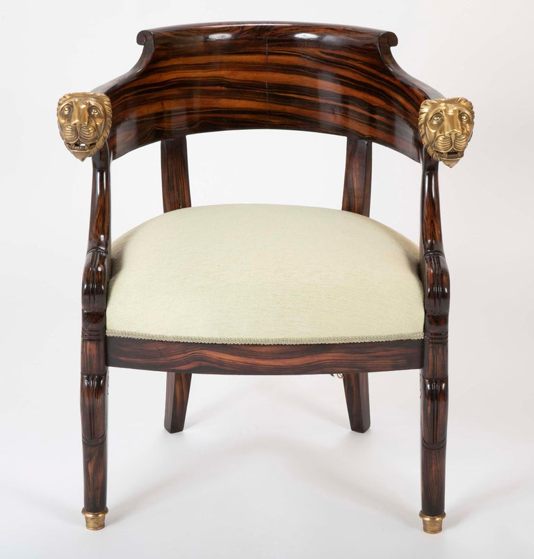Mid-20th century English faux calamander veneer barrel chair with bronze lion's head hand rests. In the manner of the Empire period.