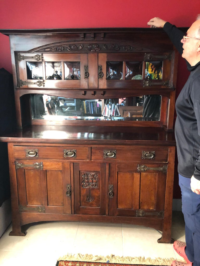 A fine English antique two part mahogany side board, buffet, or cabinet constructed in two parts, top and bottom. Features original Arts & Crafts tulip strap hinges and pulls hardware with 2 over 2 doors in the bottom section and 2 doors in top