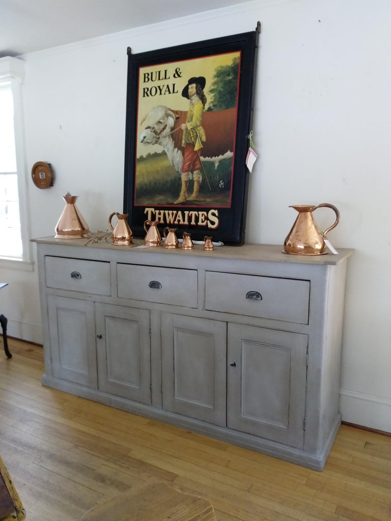A gorgeous light grey painted English base with a light scrubbed pine top. This large piece has metal pulls on its three drawers, combined with two locks and keys for its four doors. If that weren't enough, there is also much storage space available
