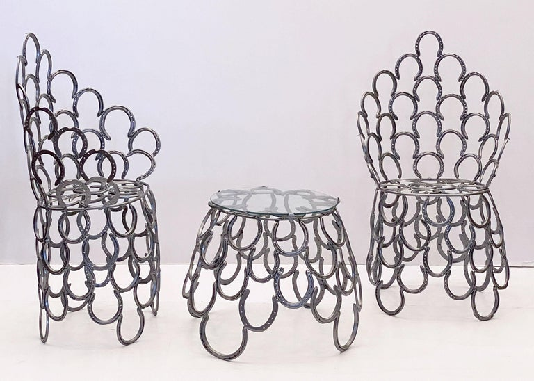 A lovely English garden set (includes table and two chairs) - each piece featuring a decorative design of iron horseshoes that together create a very comfortable seating. The table includes an optional fitted round glass top  Table dimensions: