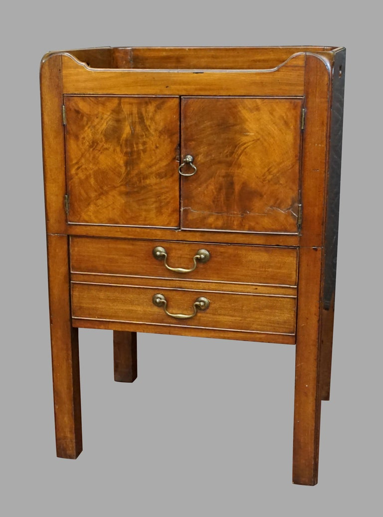 A George III figured mahogany bedside commode of typical form, the shaped top with side carrying handle cutouts, above a pair of cupboard doors over a single pull out drawer all resting on square legs. Circa 1800-1820.