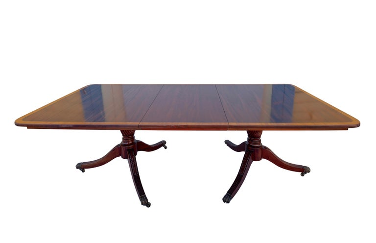 A large and unusually wide mahogany double pedestal dining table with satinwood inlay trim. The table has two leaves measuring 24 inches each. In excellent condition, professionally restored and refinished sometime in the 1970s.