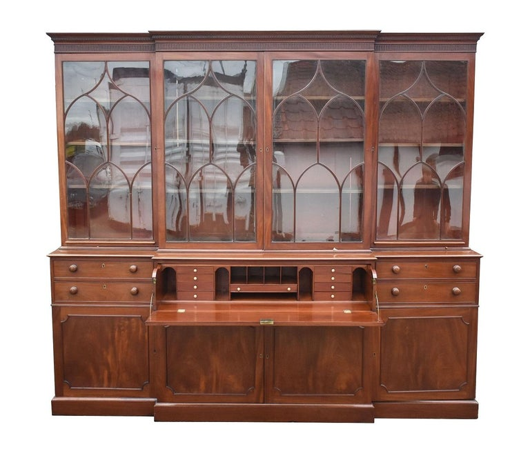 For sale is a fine quality George III Mahogany Secretaire Breakfront Bookcase. Have four doors with arched oval glazing bars open to adjustable interior shelves. Below this, the base has a large secretaire drawer to the centre, with a drop front