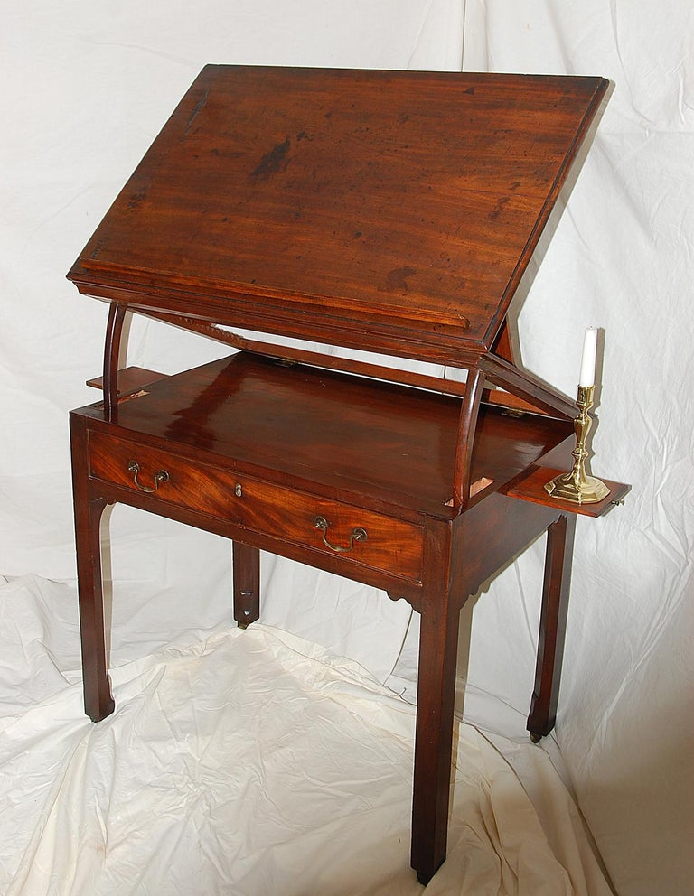 This English Georgian Chippendale period architect's table in mahogany has two side candle slides, a long drawer, and a rising top. The top has a feature that allows it to rise using a double articulating mechanism. There is a removable paper rest