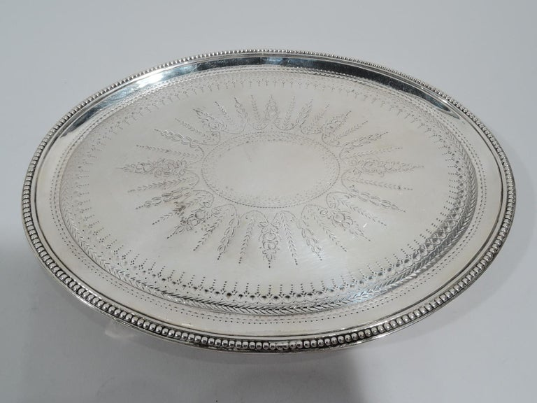 George III sterling silver salver. Made by Elizabeth Jones in London in 1784. Each: Oval with beaded rim and 4 beaded triangular supports. Neoclassical ornament including large central patera (vacant) engraved on well. Fully marked. Weight: 13 troy