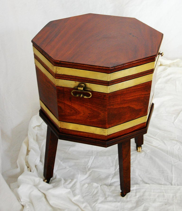English Georgian period Chippendale mahogany octagonal cellarette on original base with brass side handles and brass strapping. This cellarette retains its original interior with divisions for bottles and original lining. There is a professional