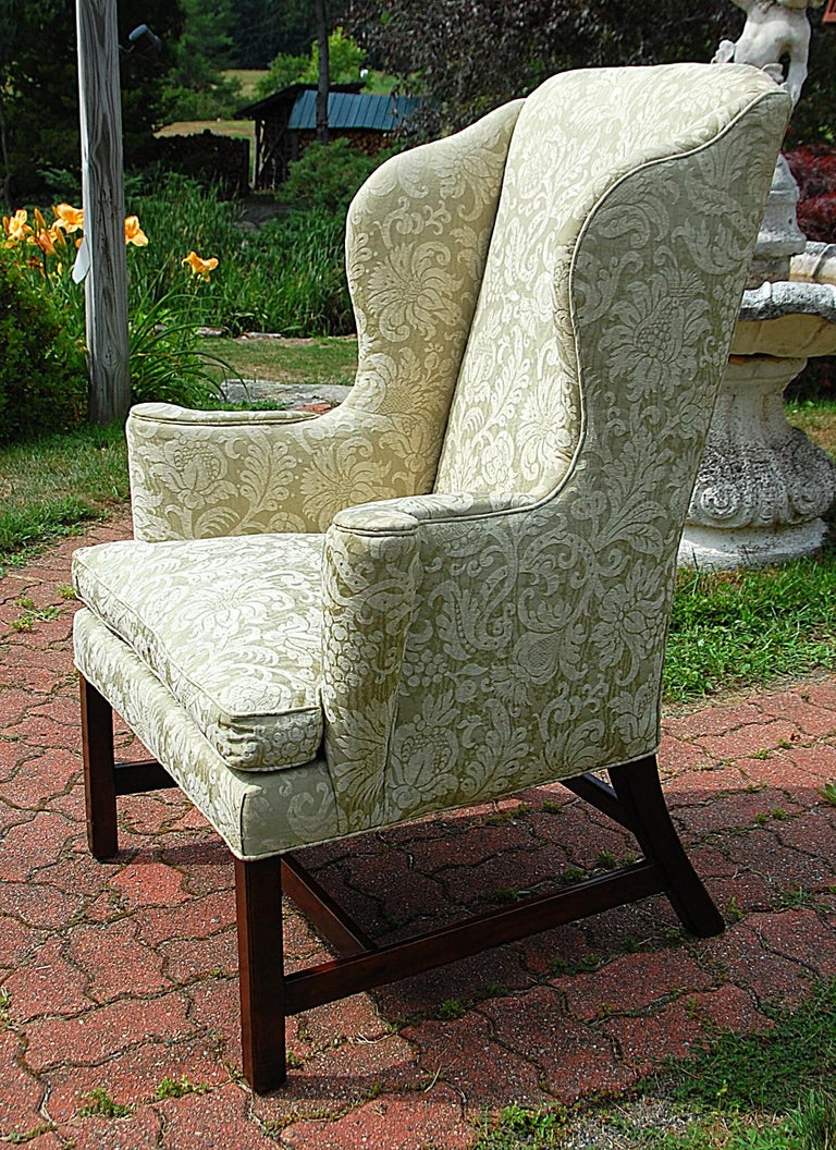 English Georgian period Chippendale mahogany wing chair with square molded legs, H-stretcher, out swept arms, shaped tall back, serpentine shaped wings, loose cushion. The celadon and cream colored damask upholstery is not new, circa 1800. $3,950.