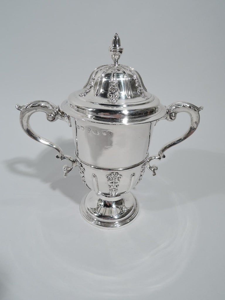 George II sterling silver covered urn. Made by John Langlands & John Robertson in Newcastle in 1739. Girdled with leaf-capped double-scroll sides handles and raised foot. Cover domed with acorn finial. Applied vertical strapwork alternating with