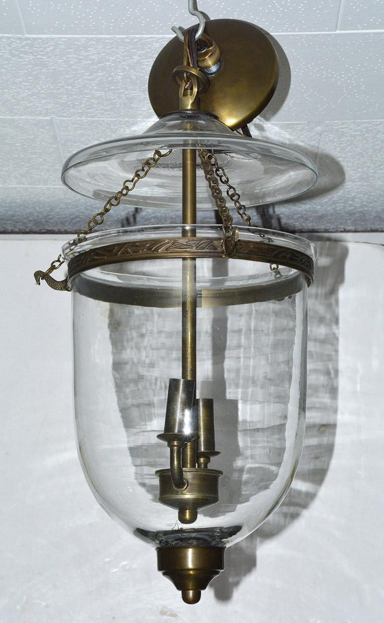 Vintage English Georgian style clear glass hanging pendant lantern suspended by chains from a glass cover and brass ring. Two light interior cluster lights. Bell Jar hanging chandelier or hall light. It arrives ready to install with brass ceiling