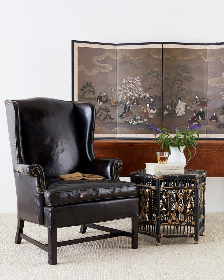 Stately English George III style wingback armchair finished in dark chocolate brown leather hides. The wing chair features fully developed wings and is accented by brass tack nail heads on the borders. Constructed from a hardwood frame with an