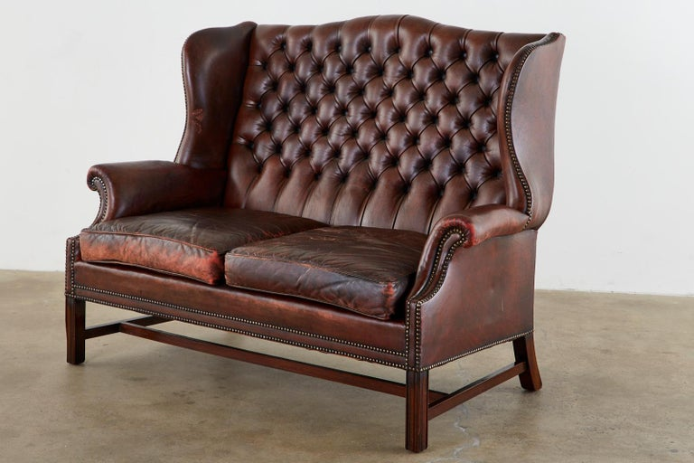 Beautifully aged English Chesterfield wingback settee or sofa. Featuring a tufted cordovan leather upholstery bordered by brass tack nailheads. The mahogany frame made in the Georgian taste features English rolled arms and large fully developed