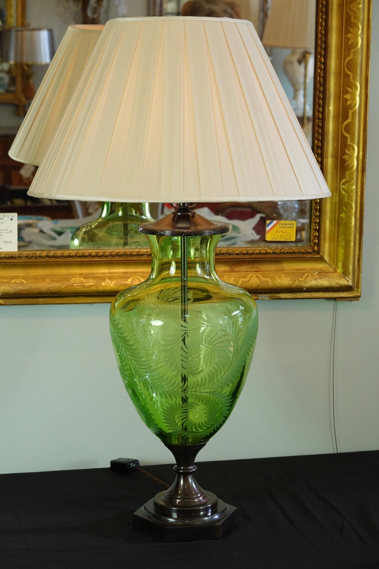 Light green crystal urn-form lamp with etched fern leafs design by Lucy Cope. The lamp was handmade in England and is wired for the US. The lamp features patinated bronze octagonal base and vase cap with reed and ribbon design. Included new pleated