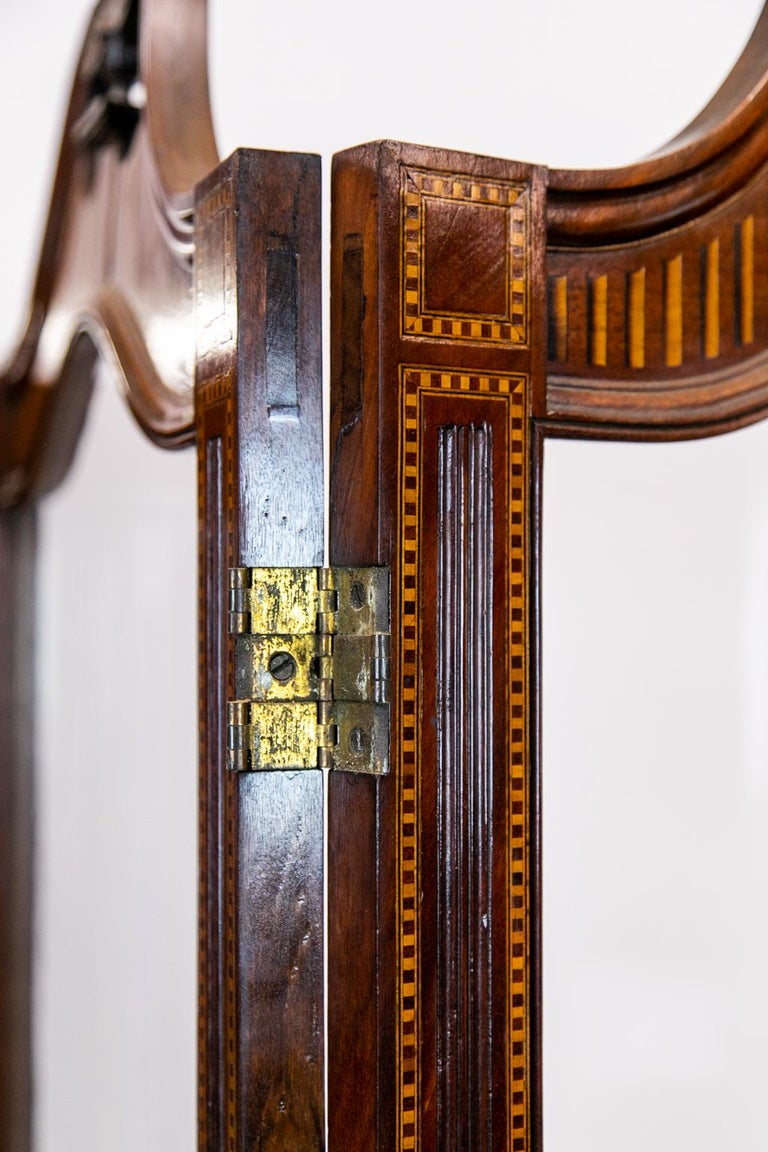 English inlaid four paneled folding screen made of mahogany inlaid with satinwood. It has walnut bandings bordered by boxwood and ebony line inlay. There is a carved molded panel inside the inlay lines and a swan neck broken pediment crest with urn