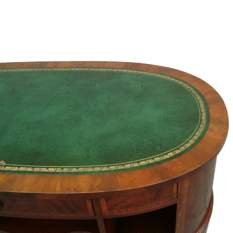 English oval coffee table with embossed leather top, side and central shelves and drawers on base, circa 1940s.  Measurements: Length 50