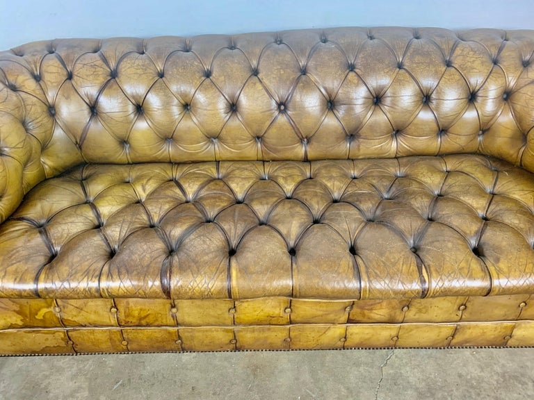 Handsome English leather tufted Chesterfield style sofa with lion paw feet and nailhead trim detail. The leather is beautiful worn with distressing throughout showing the history it has had along the way. Light tobacco color.