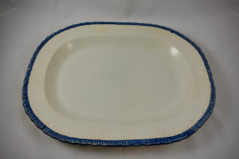 A heavy Leeds style oval platter, a pearlware or creamware body with a deep blue edge called feather or shell, circa 1825–1840, Staffordshire, England. A good clean front surface with a lightly combed back.