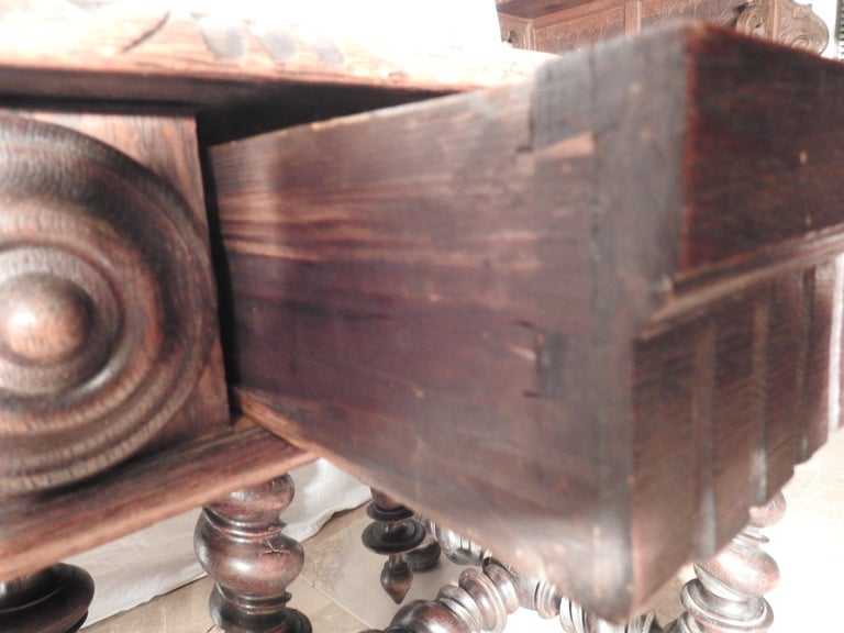 Offering this unmatchable English library table. Having barley twist legs and stretchers this table has a substantial base it sits atop. Around the edge of the table it has medallions and two drawers to one side. Made of walnut and stained in a dark