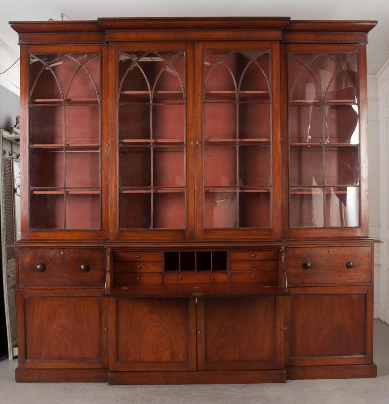 An incredible breakfront bookcase, made of mahogany in the Georgian style, with incorporated desk. Made circa 1810, this stunning English piece has three glass-front upper cabinets set above a cased plinth base. The upper cabinets have all of their