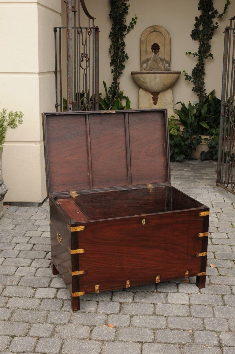 An English mahogany brass-bound Campaign trunk from the second half of the 19th century, with lateral handles. Born during the third quarter of the 19th century, this English Campaign trunk features a stylish linear mahogany structure, accentuated
