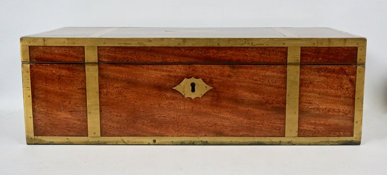 An English mahogany campaign style brass bound traveling desk with recessed handles and a long exterior side drawer, the interior with a velvet lined writing slope, inkwell, pen compartments and letter wells. The top has a cut brass central