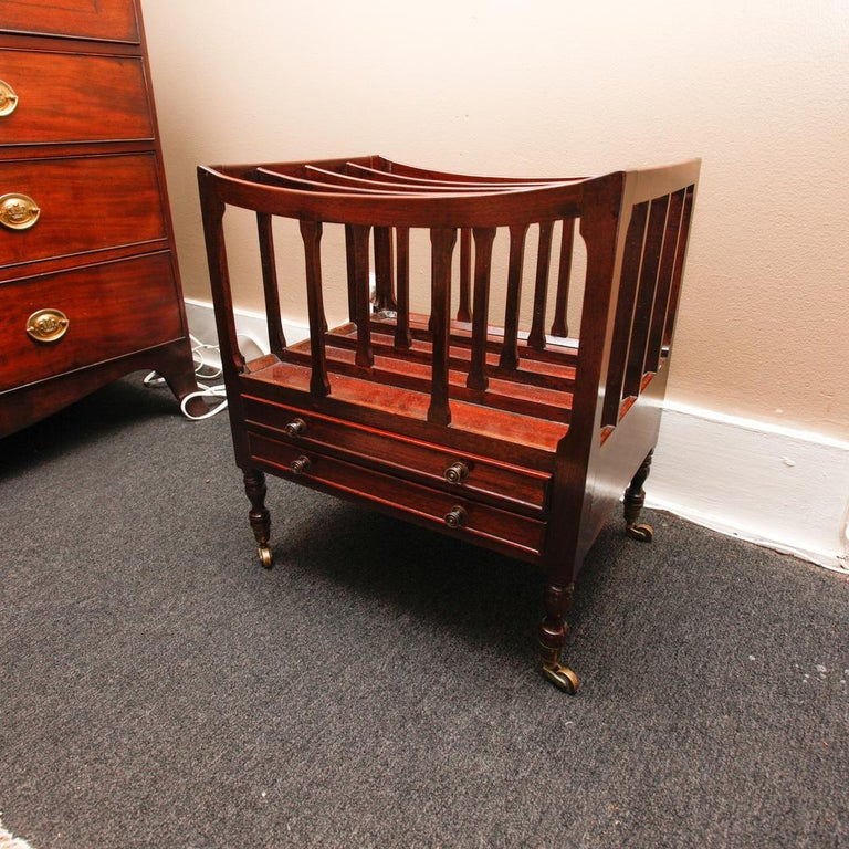 Late 19th century English mahogany Canterbury or folio rack with three open slats over a drawer and resting on turned legs with brass casters.