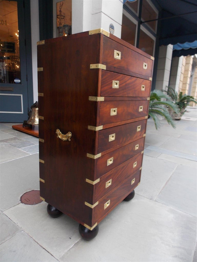 English mahogany military campaign seven drawer tall chest with original brass side handles, brass mounts, recessed brasses, and resting on the original bun feet, Late 19th century.
